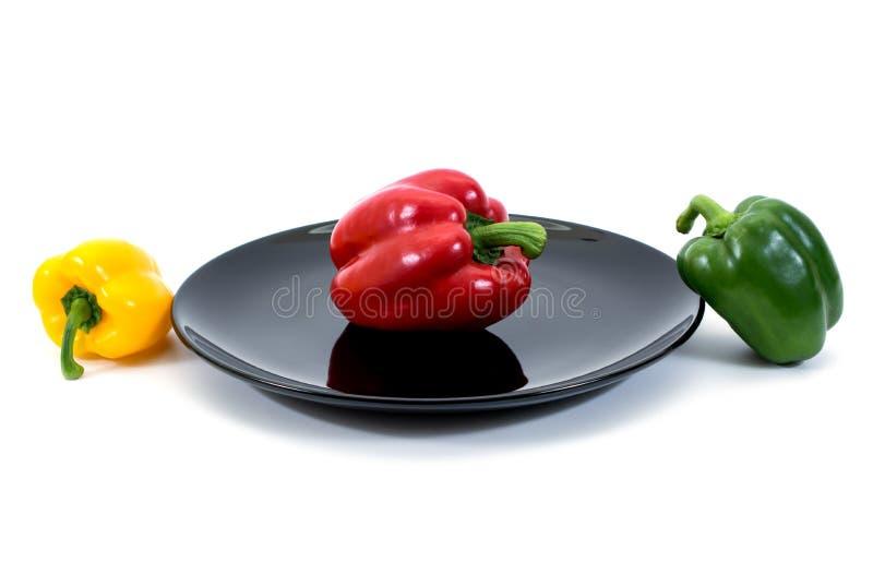 Paprika i en platta över vit Spanska peppar i den isolerade plattan royaltyfria foton