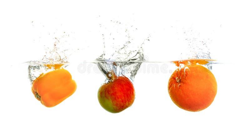 Paprika, manzana y naranja en agua imagen de archivo