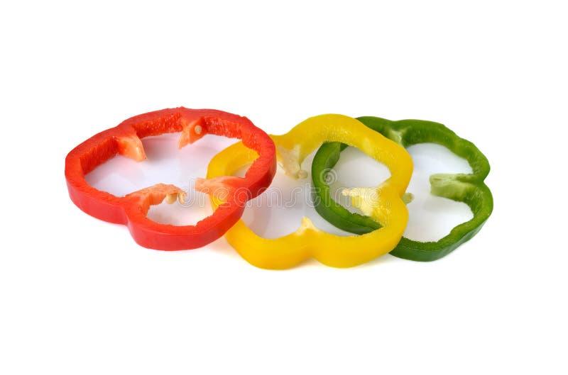 Paprika rouge coupé en tranches de vert jaune sur le blanc image stock
