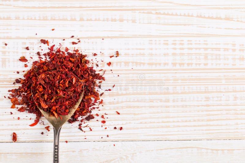 Paprika tritata in un cucchiaio di ferro su fondo bianco Copia spazio fotografia stock