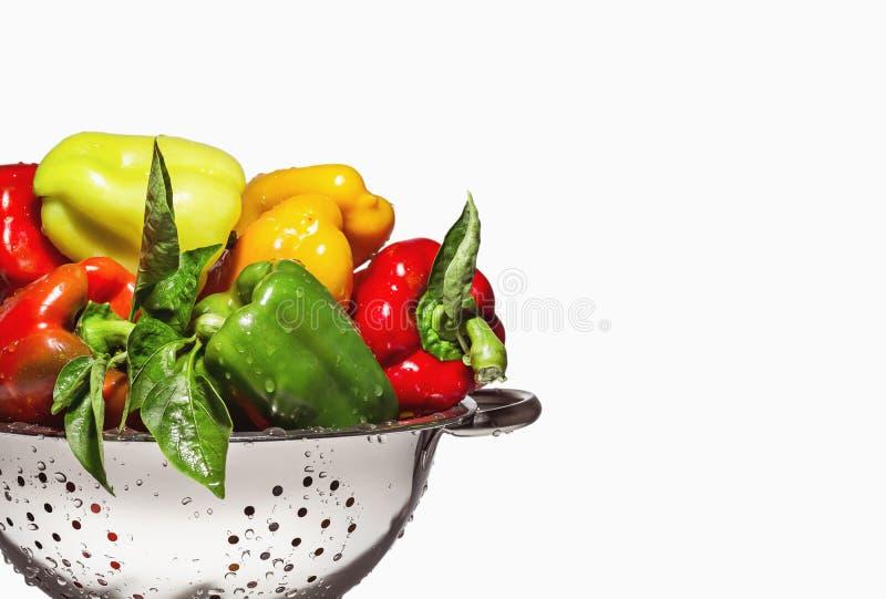 Paprikas colorés mélangés frais dans une passoire d'isolement sur le blanc photo stock