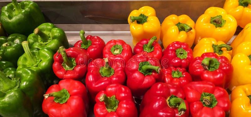 Paprikas doux colorés dans la texture de fond du marché dans l'ordre vert rouge jaune photos libres de droits