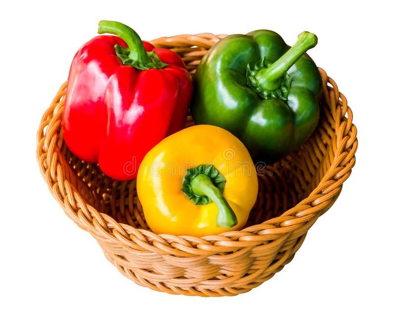 Paprikas dulces rojos, verdes y amarillos en una cesta aislada en el fondo blanco con la trayectoria de recortes imágenes de archivo libres de regalías