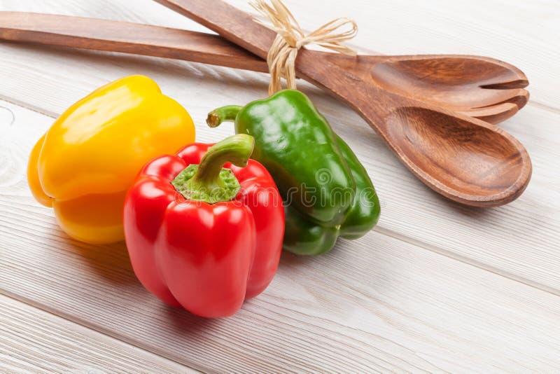 Paprikas et ustensile colorés de cuisine photographie stock