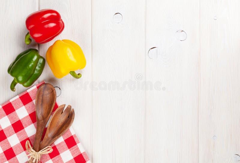 Paprikas et ustensile colorés de cuisine photos stock