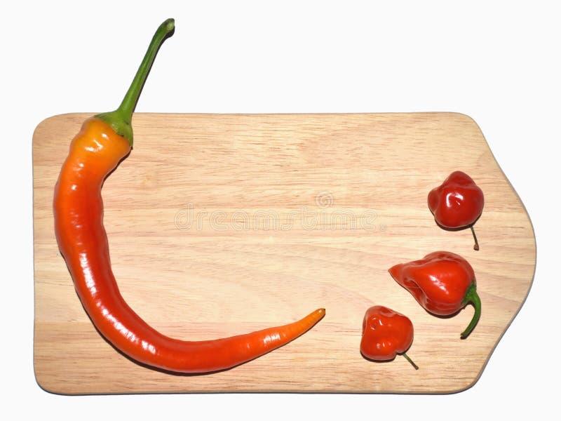 Paprikas, roter Pfeffer auf hölzernem Brett stockbild