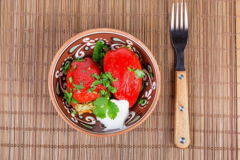 Paprikas rouges bourrés cuits dans la cuvette et la fourchette d'argile photographie stock