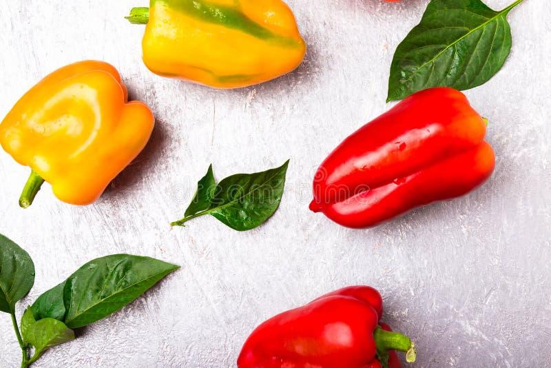 Paprikas rouges, oranges et jaunes sur le fond gris Légumes organiques sains Vue supérieure Art Border Design Vue photos libres de droits