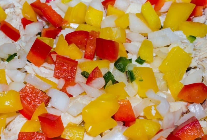 Paprikas verdes, rojos y amarillos vibrantes con la cebolla y el pollo imagen de archivo