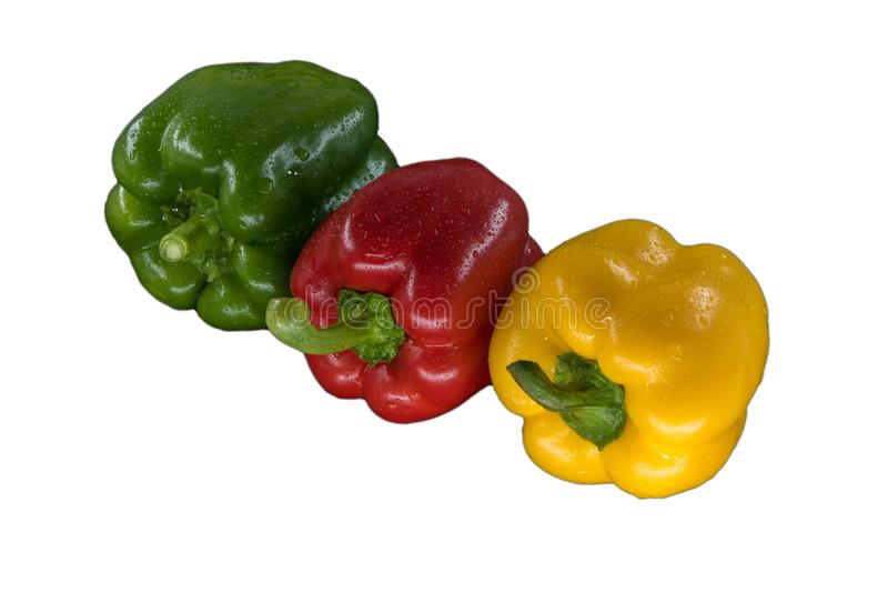 Paprikas verdes y amarillos rojos aislados en el fondo blanco, cierre para arriba imagen de archivo