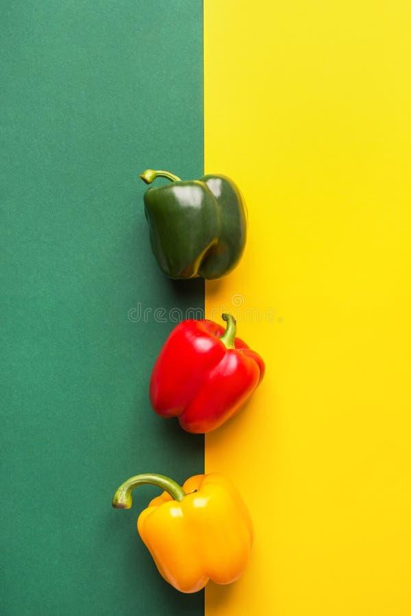 Paprikas verts jaunes rouges colorés de légumes organiques mûrs sur le fond de duotone R?gime bas? par usine saine image libre de droits