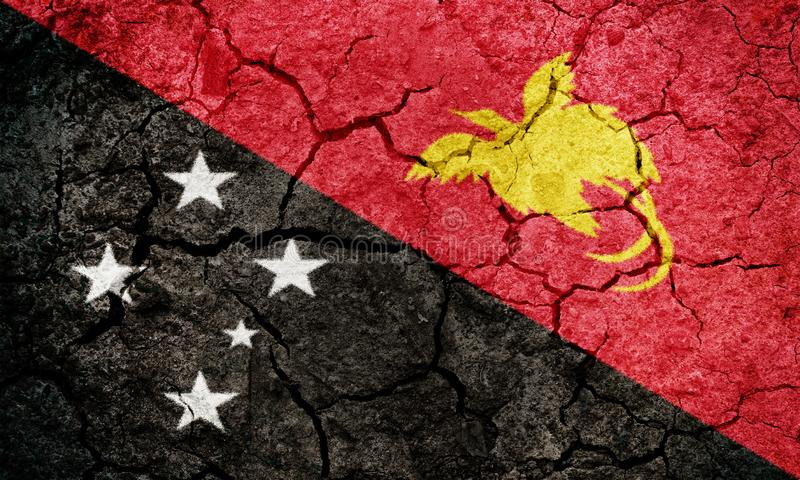 Papua New Guinea flag. Independent State of Papua New Guinea flag on dry earth ground texture background stock photo