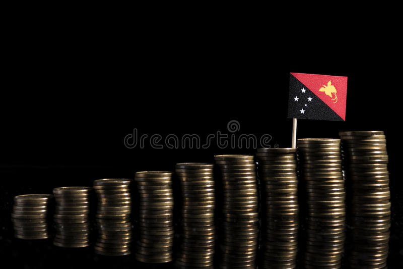 Papua New Guinea flag with lot of coins isolated on black background royalty free stock image