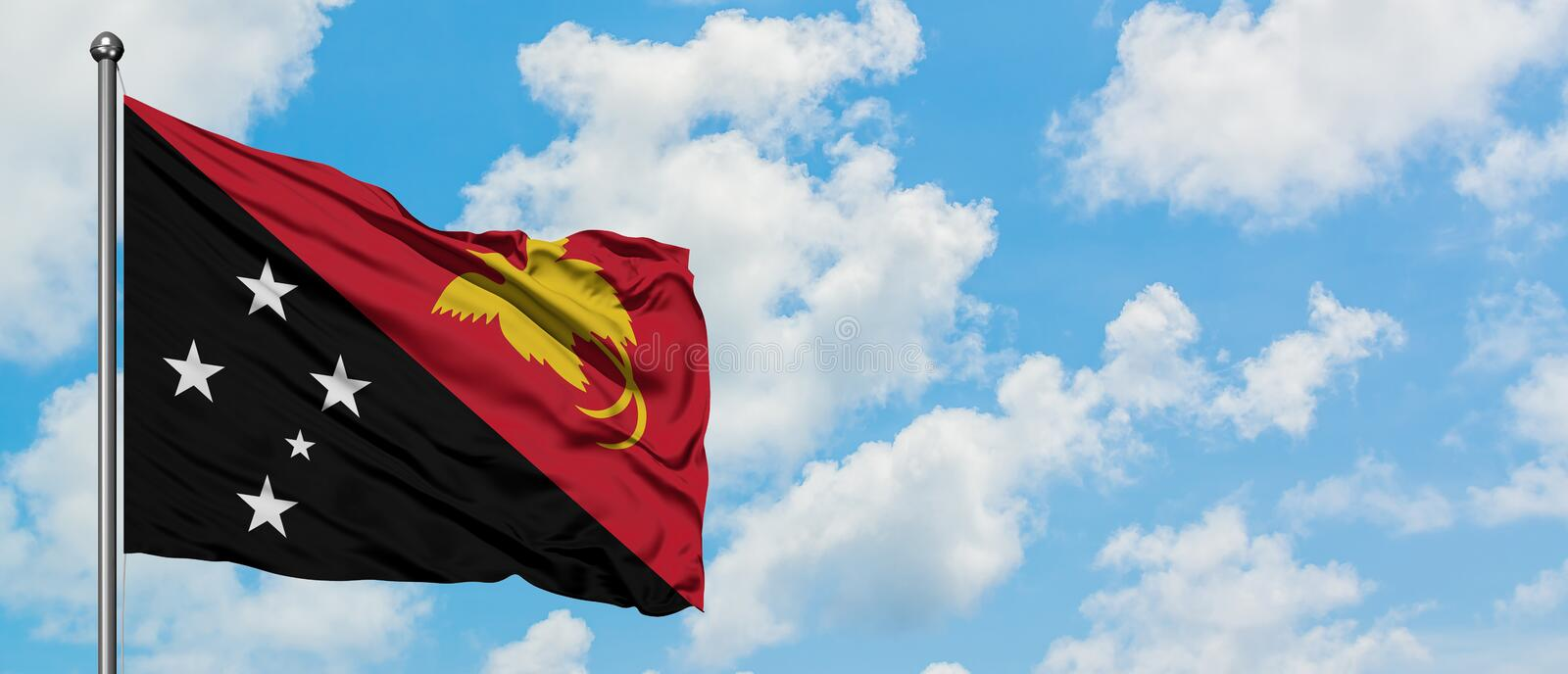 Papua New Guinea flag waving in the wind against white cloudy blue sky. Diplomacy concept, international relations.  stock image