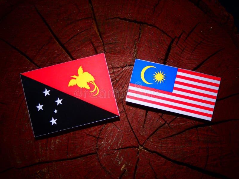 Papua - nowa gwinei flaga z malezyjczyk flaga na drzewnego fiszorka isolat zdjęcia royalty free