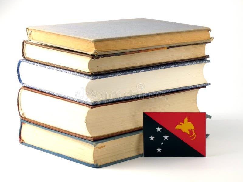 Papua - nowa gwinei flaga z stosem książki odizolowywać na białym backg zdjęcia royalty free