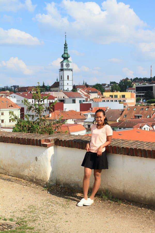 Papuan flicka med stadstornet i Trebic bakom royaltyfri foto