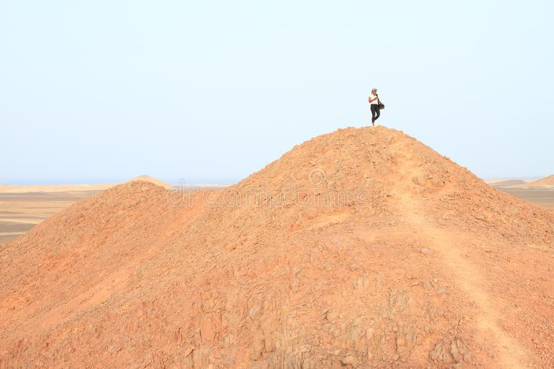 Papuan girl on top of hill in desert in Marsa Alam stock photo