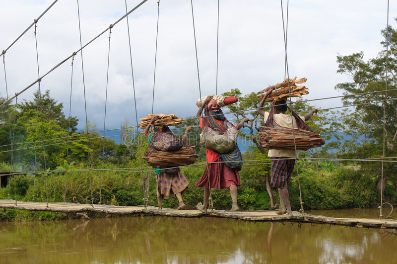 Papuan women crossing bridge, Wamena, Papua stock photo