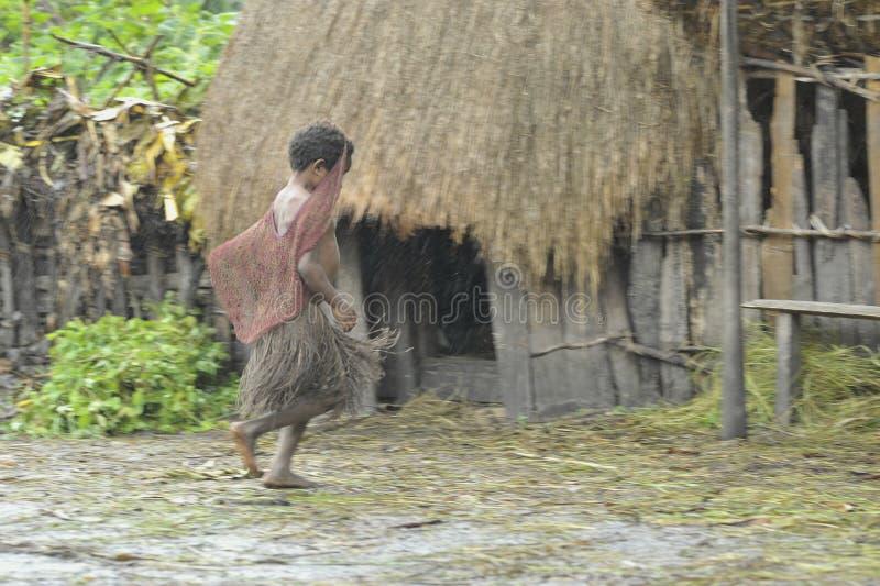 Papuanflickan från den Dani stammen skynda sig för att dölja från ett regn under ett tak. royaltyfri fotografi