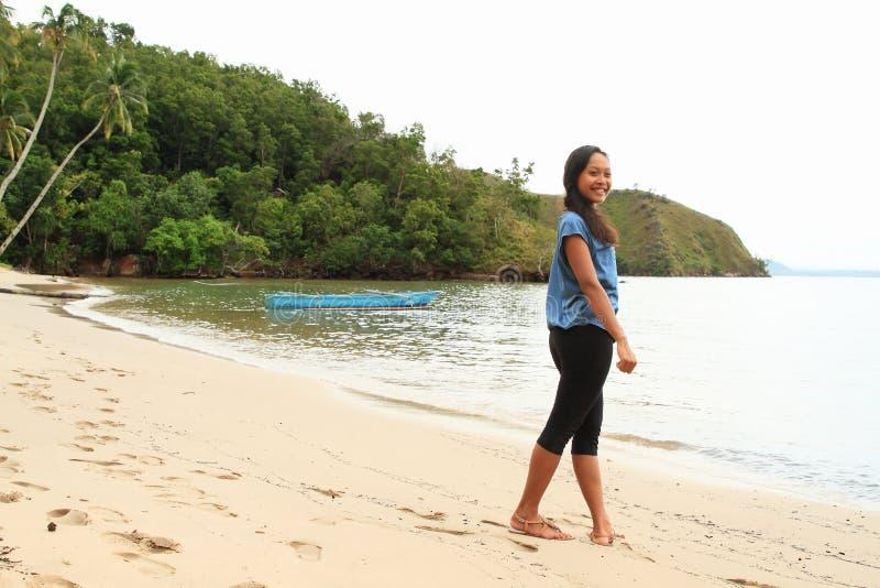 Papuanmeisje die op strand lopen stock foto