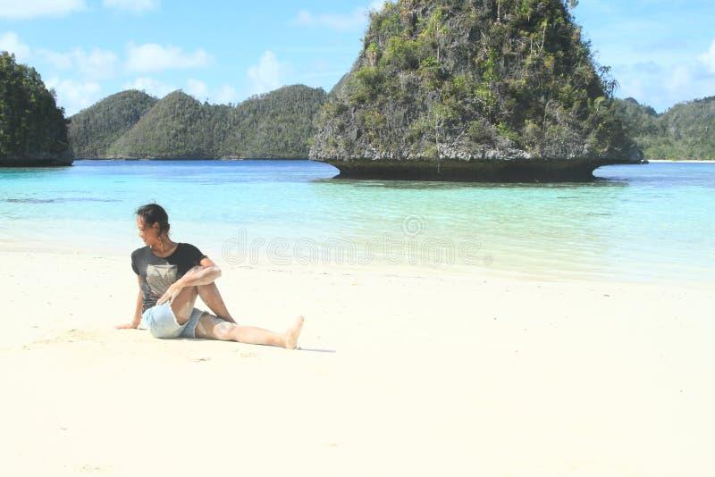 Papuanmeisje opleidingsyoga op strand in Wayag stock afbeeldingen