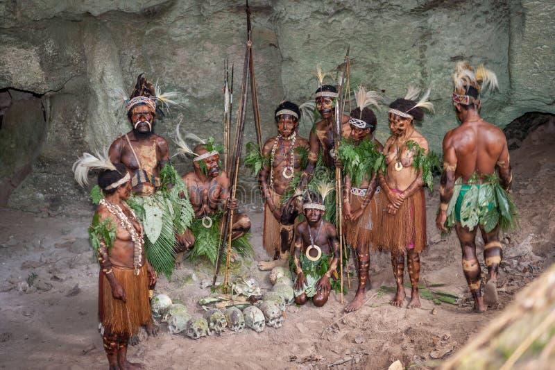 Papuans med ben och skallar Folket av en Papuanstam av Yafi i traditionell kläder, prydnader och färgläggning royaltyfria bilder
