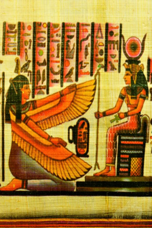 Papyrus Egyptian girl with wings on her knees in front of the ruler royalty free stock photos