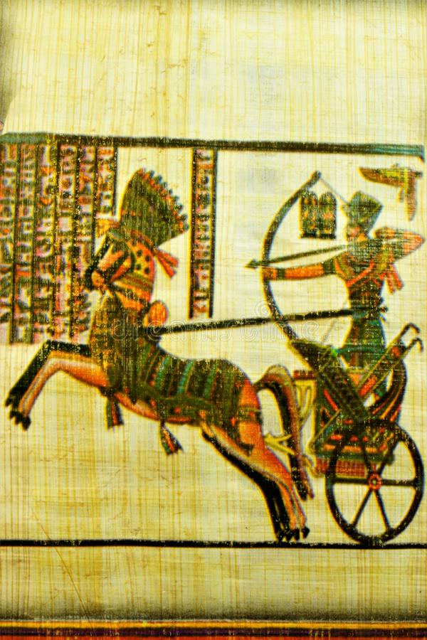 Papyrus Egyptian warrior with a bow on a chariot. royalty free stock photography