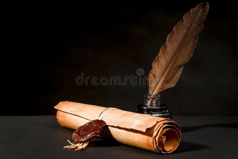 Scroll of a papyrus with a seal, a feather and an inkwell stock photos