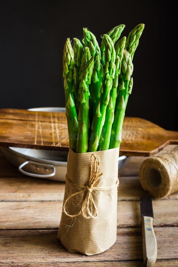 Paquet d'asperge verte fraîche enveloppée en papier de métier attaché avec la ficelle se tenant sur la table de cuisine en bois photo stock