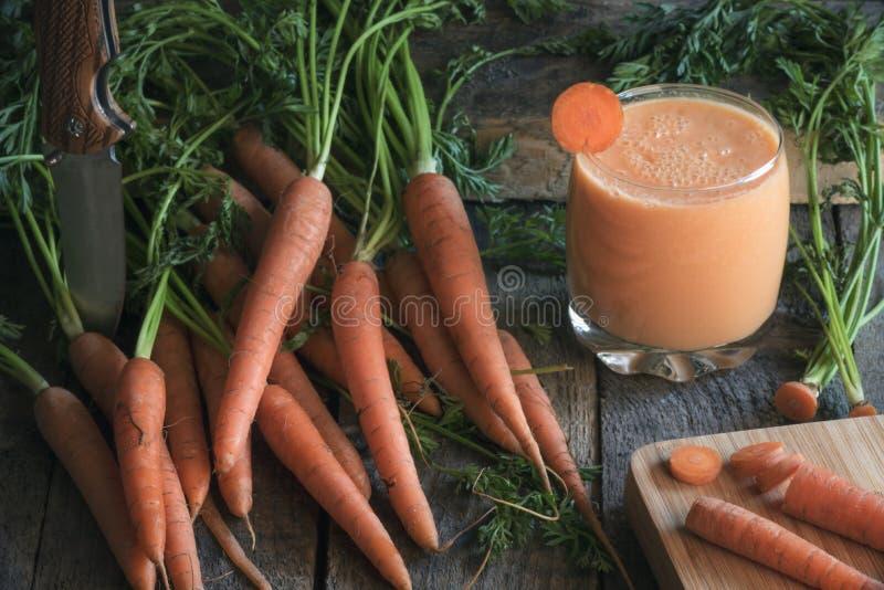 Paquet de carottes et d'un verre de jus frais images libres de droits