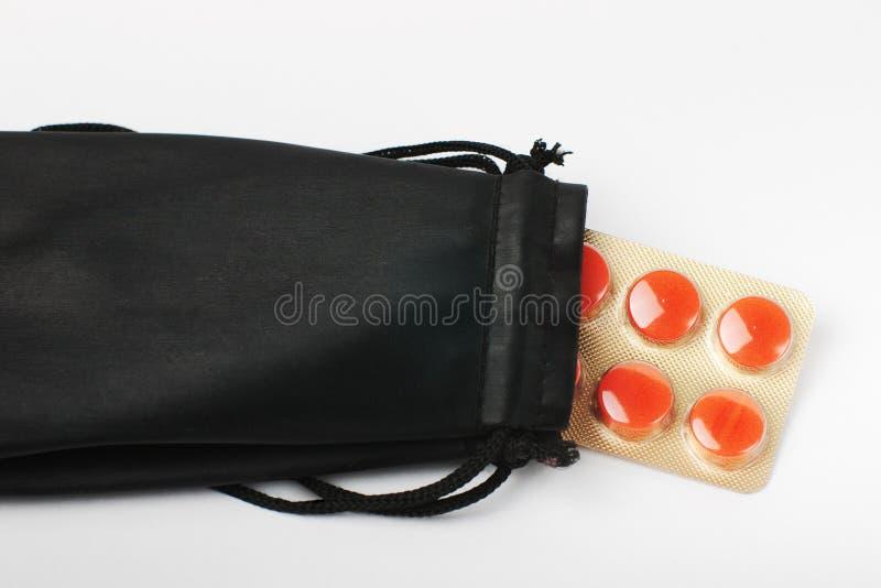 Paquet de pillules rouges collant hors du sac noir photos stock