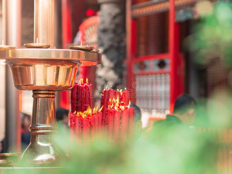Paquet de plan rapproché de grandes bougies rouges brûlant près du plateau d'or chez Longshan Temple photographie stock libre de droits