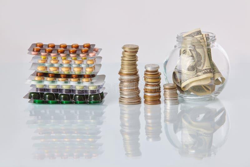 Paquet des pilules de médecine avec trois paquets de pièces de monnaie et de la bouteille en verre avec l'argent d'argent liquide photographie stock libre de droits