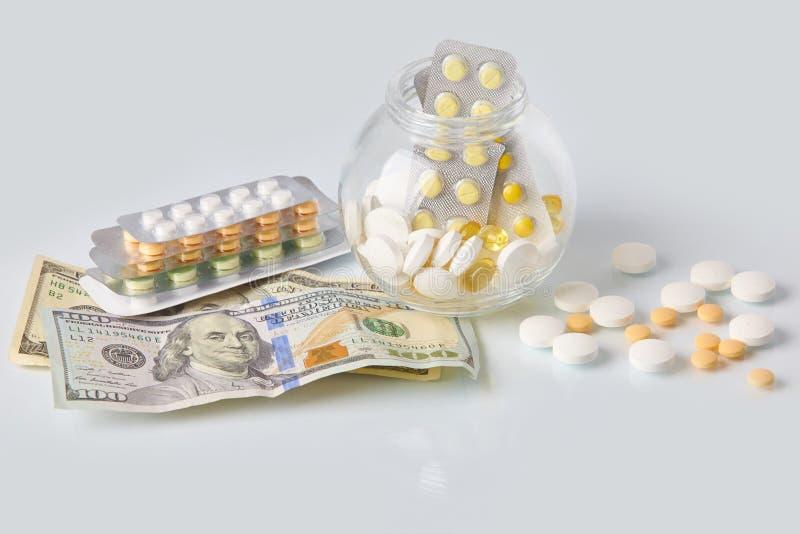 Paquet des pilules de médecine avec trois paquets de pièces de monnaie et de la bouteille en verre avec l'argent d'argent liquide photo libre de droits
