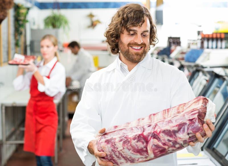 Paquet heureux de Looking At Meat de boucher image libre de droits