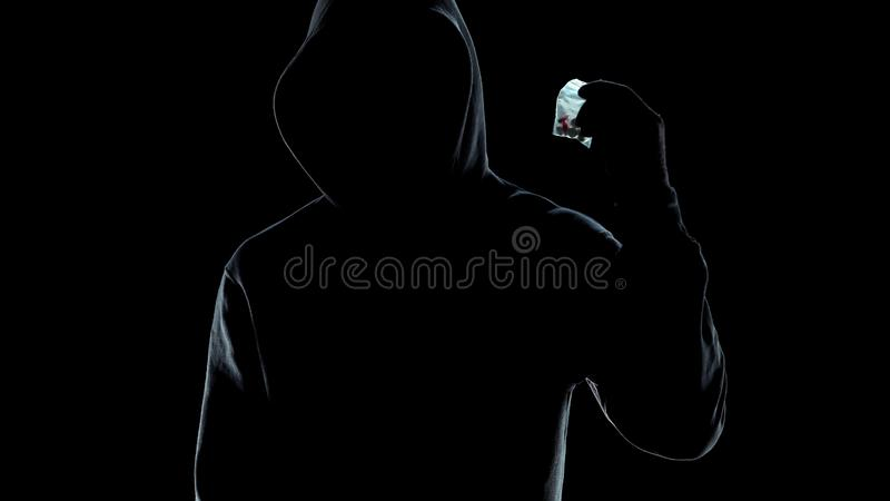Paquet masculin de participation de silhouette avec des pilules, crime de trafic de stupéfiants, mode de vie image libre de droits
