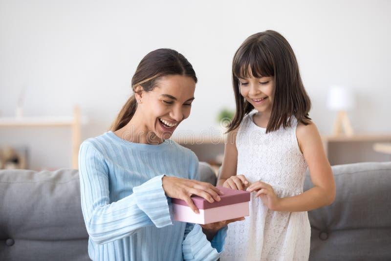 Paquet ouvert d'anniversaire de maman heureuse avec la fille mignonne photographie stock