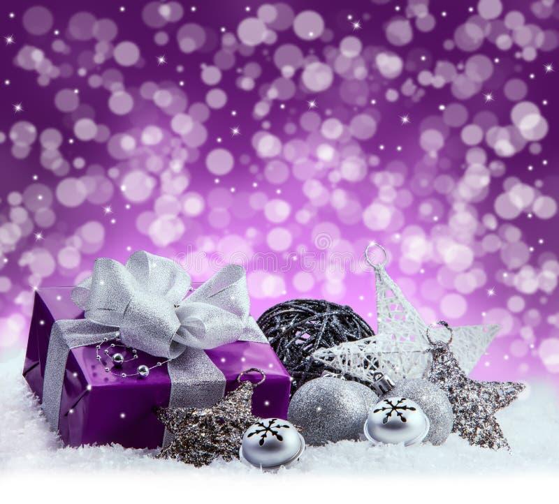 Paquet pourpre de Noël, cadeau d'un ruban argenté Les tintements du carillon, les boules argentées de Noël et le Noël tient le pr photos libres de droits