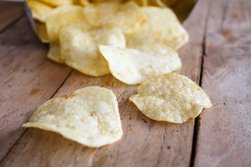 Paquete abierto de patatas fritas deliciosas en la madera imagen de archivo