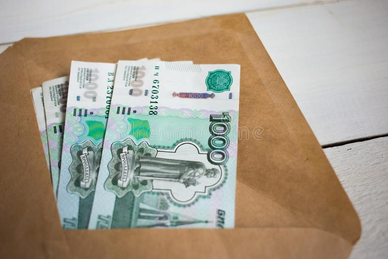 paquete ascendente cercano de billetes de banco rusos del dinero mil rublos en sobre en la tabla de madera imágenes de archivo libres de regalías