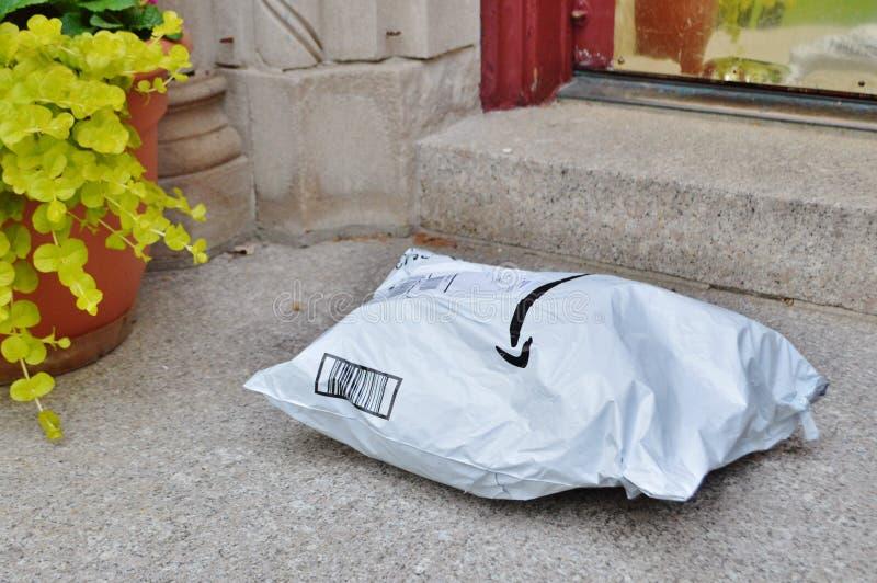 Paquete casero enviado entregado al umbral de la casa del cliente imagenes de archivo