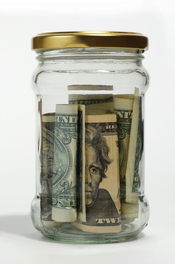 Paquete de dólares americanos en un tarro de cristal cerrado Una de las maneras de almacenar el dinero fotografía de archivo