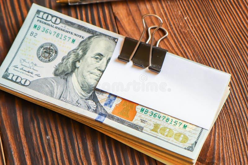 Paquete de d?lares y de la etiqueta engomada del Libro Blanco en el texto o el texto fotos de archivo libres de regalías