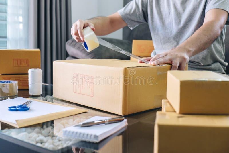 Paquete de la pequeña empresa para el envío al cliente, hombre independiente de la PME del empresario joven que trabaja con el em imagenes de archivo