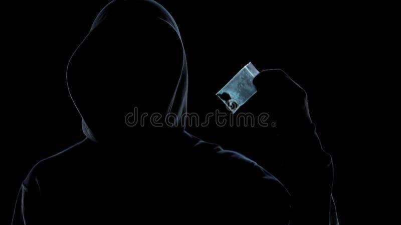 Paquete de la tenencia del drogadicto con la marijuana, hábito mortal, tráfico ilegal imagenes de archivo