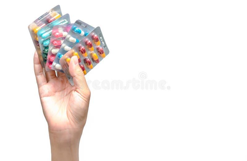Paquete de la tenencia de la mano de píldoras antibióticos de la cápsula aisladas en el fondo blanco Dando o recibiendo la droga  foto de archivo