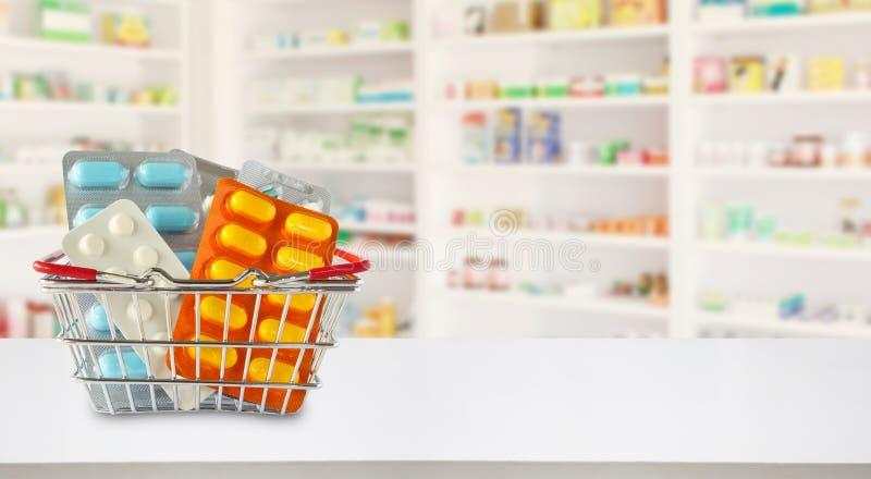 Paquete de las píldoras de la medicina en cesta de compras con el fondo de la falta de definición de la farmacia fotos de archivo libres de regalías