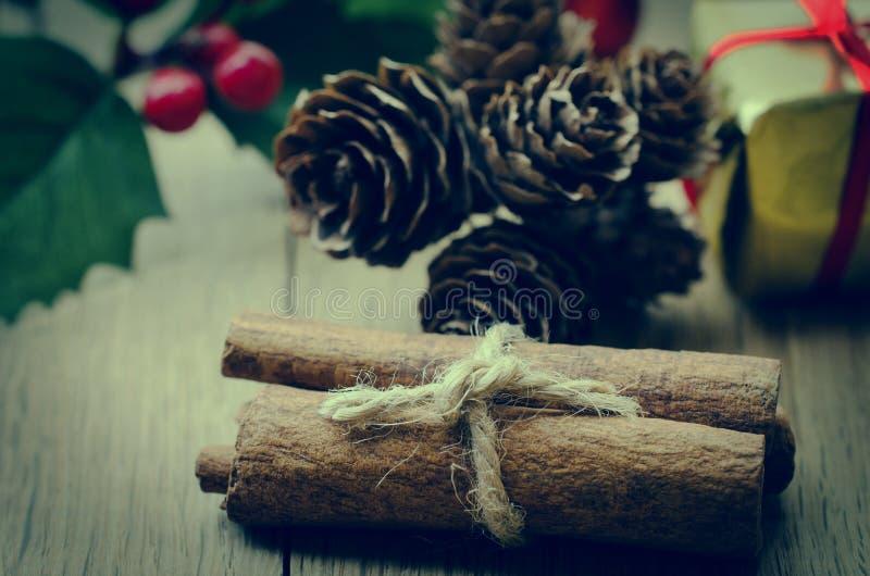 Paquete de los palillos de canela, acebo y conos de abeto en la tabla de Planked del roble foto de archivo